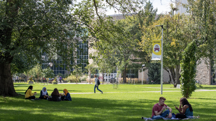 Students sitting on lawn in front of Engineering building at McMaster University